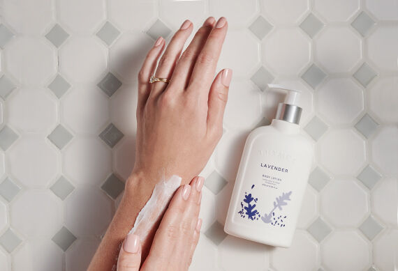 Thymes Lavender Body Lotion bottle next to hand rubbing in lotion