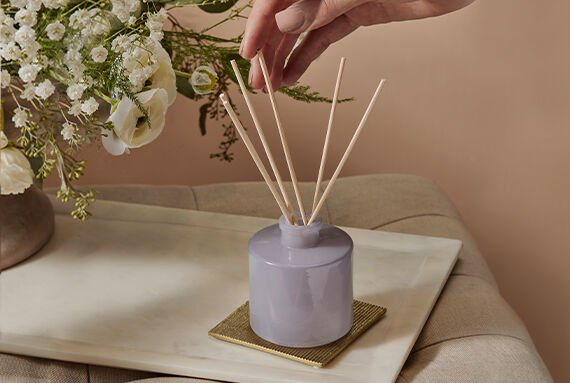 lavender reed diffuser and reeds being arranged