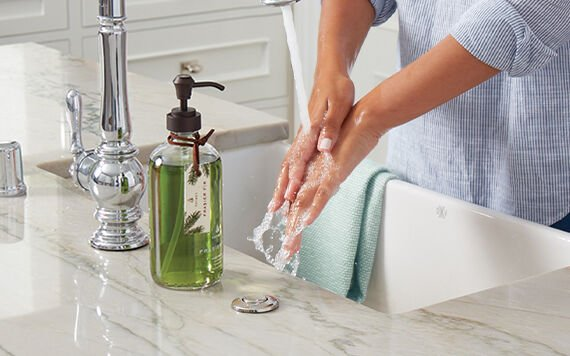 Sink with large hand wash and woman washing hands