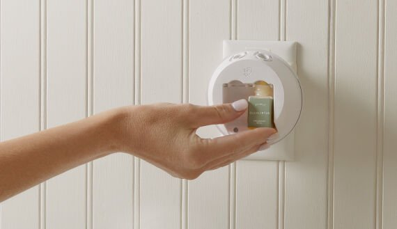 Thymes Fragrance Pura Vials being inserted in a Pura smart home diffuser